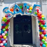 "Multi Colored arch with ""SALE"" in silver foil balloons"